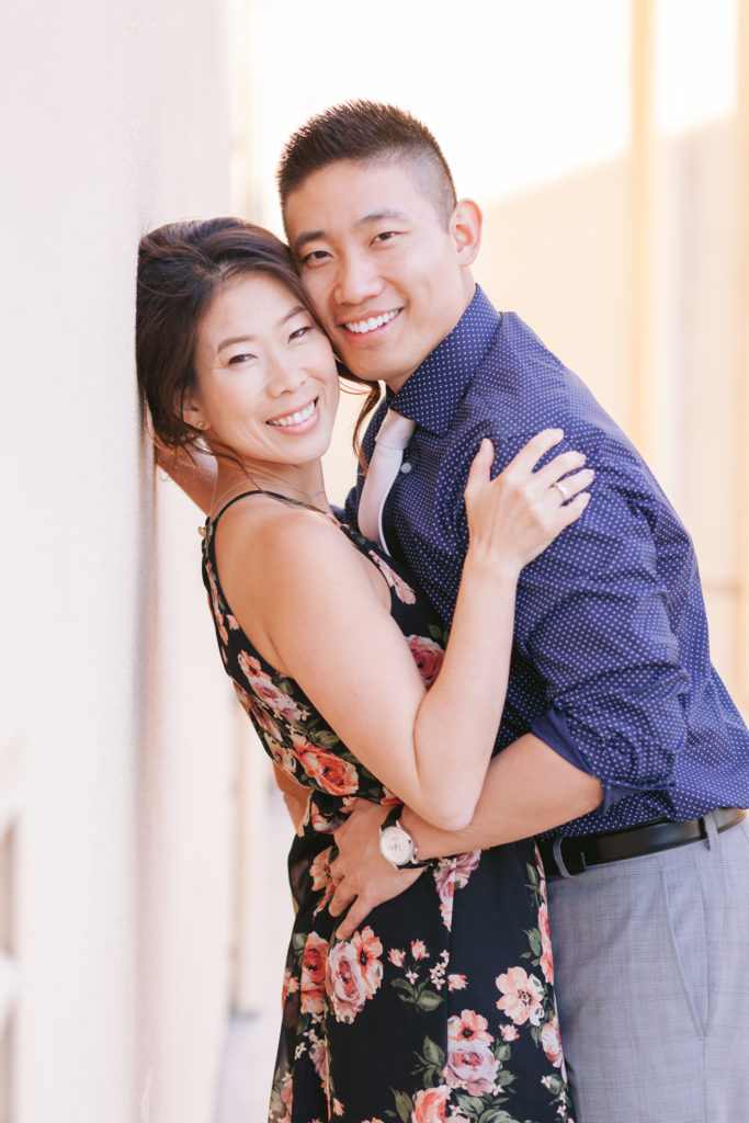couple smiling back against wall